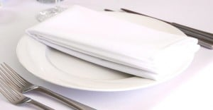 white table napkin folded neatly on top of a white plate