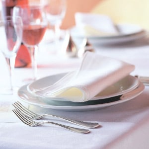 Fine dining white table linen setting.