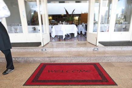A resturant entrace with a red welcome mat