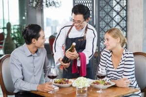 Smiling Asian Waiter Offering Wine to Young Couple