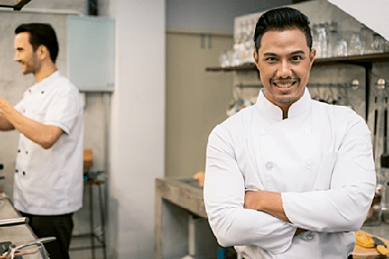 Smiling man wearing a white clean chef uniform