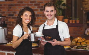 Two smiling restaurant employees wearing a well maintained black apron uniforms