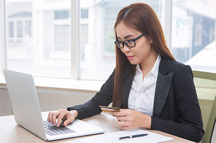 Side view of a young employee wearing glasses working in front of her laptop.