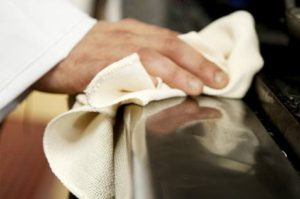 A man cleaning the kitchen using a cloth towel.