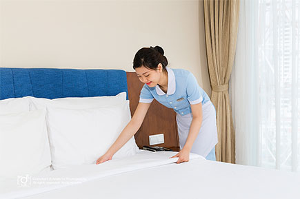 Housekeeping attendant fixing the hotel bed