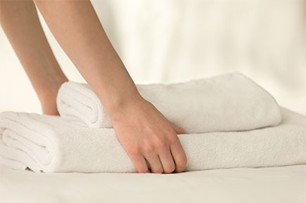 Close up of a hand holding a stack of fresh, clean towels.