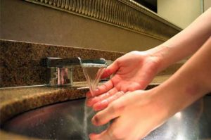 Wahing hands using hand soap.
