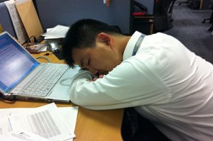 Fatigued employee sleeping at his work desk.