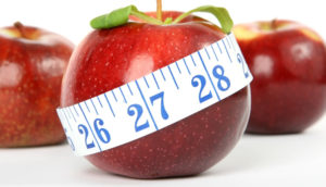 Close up of a red apple with tape measure