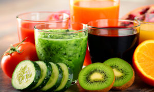 Glasses of fresh juices and fruits around them.