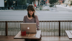 A middle aged woman working on a laptop outside a cafe.